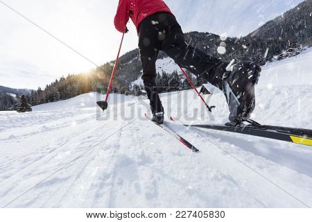 Man cross-country skiing during sunny winter day, winter sport.