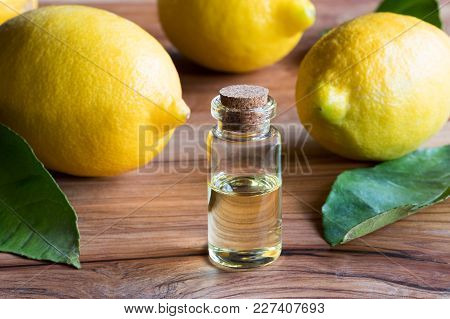 A Bottle Of Lemon Essential Oil With Fresh Lemons And Leaves In The Background
