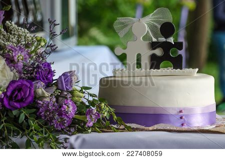 Wedding Purple Flower Bouquet And Cake With Two Puzzle Characters Of Groom And Bride And Purple Ribb