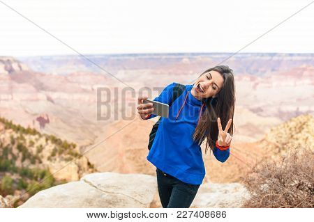 Young Beautiful Girl At Grand Canyon National Park Viewpoint, Arizona, Usa  With A Smartphone Taking