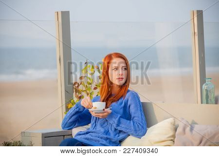 Young Redhead Girl In Bue Sweater With Cup