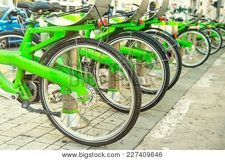Row Of Public Bicycle On Rental Station On City Background. Eco-friendly And Convenient Transportati