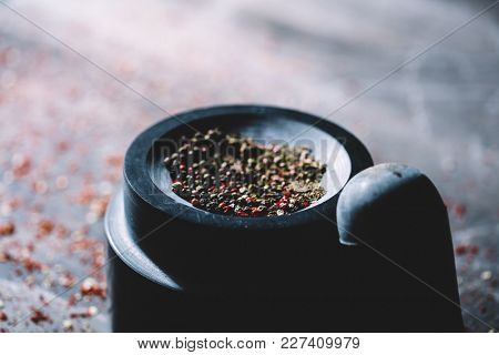 Half-crushed dried peppercorns placed in a mortar. Freshness of natural spices. Traditional ways of preparing food.