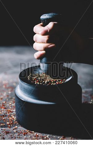 Woman's hand crushing grains of pepper in a mortar on a messy kitchen counter. Natural spices.