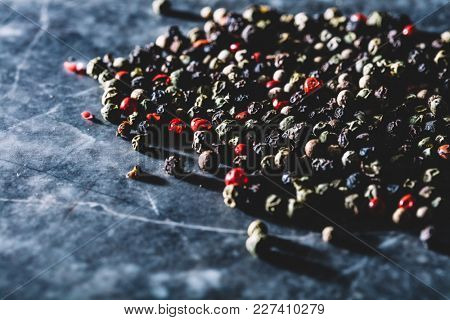 Grains of mixed pepper spilled on a marble kitchen counter. Organic spices. Peppercorns.