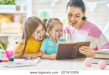 Pretty young mother and her cute daughters are reading a book. Learning to read at home.