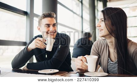 Cheerful couple enjoying coffee together in modern cafe.Drinking hot caffeine beverage on a break with business partner.Friend meeting for coffee downtown.Smiling happy people.Funny conversation poster