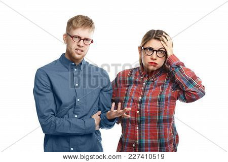 Irritated Young Female Employee In Checkered Shirt Blowing Cheeks, Having Fed Up Look, Holding Hand