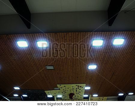 Luminous Ceiling Of Square Tiles. Wooden Ceiling With Lighting Panels. Fluorescent Lamps On The Mode