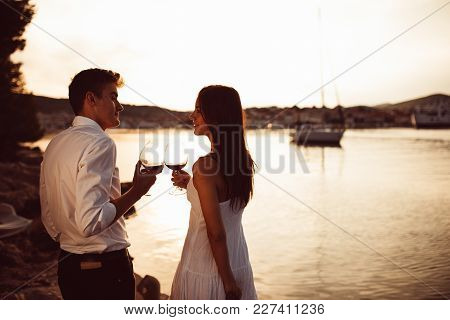 Romantic Couple Drinking Wine At Sunset At A Pier On A Seaside.romance.two People Having A Romantic