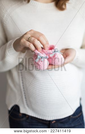 Pregnancy, Kids Fashion, Handmade Concept. There Is Close Up Of A Couple Of Lovely Baby Bootees, The