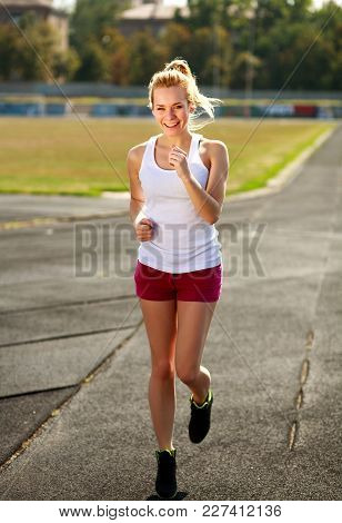 Happy Girl Jogging At A Sports Stadium Healthy Lifestyle Outdoors