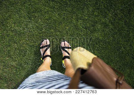 Female legs in summer sandals on green juicy grass