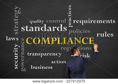 Business Person Drawing Compliance Concepts On Blackboard Background
