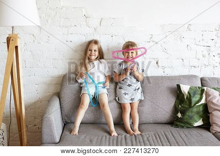 Two Mischievous Little Girls Siblings Having Fun Indoors Playing With Hangers From Mother's Wardrobe