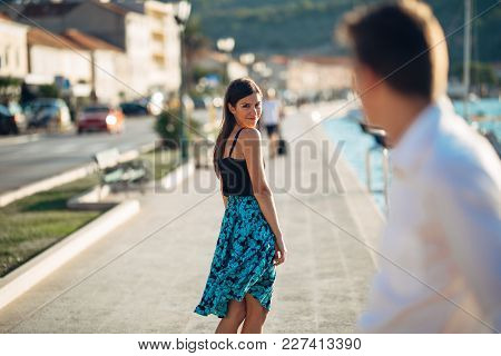 Young Attractive Woman Flirting With A Man On The Street.flirty Smiling Woman Looking Back On A Hand