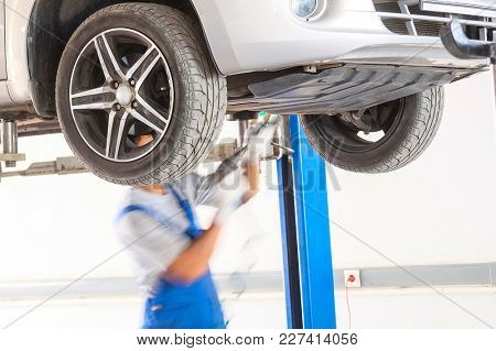 Worker works in a car repair station