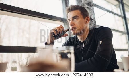 Young Man Vaping In Closed Public Space.smoking Electronic Cigarette In Cafe.nicotine Addiction.way
