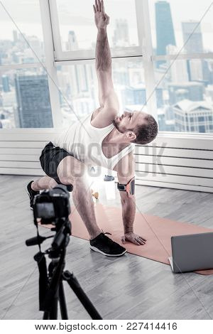 Reach Ceiling. Vigorous Male Blogger Elevating Hand While Looking Up And Filming Video