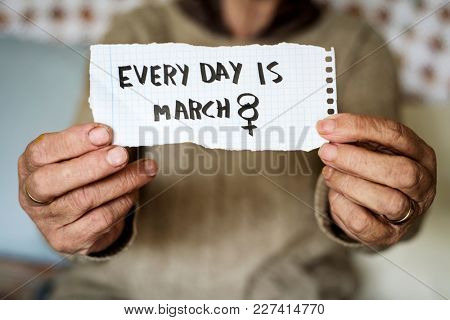 an old caucasian woman indoors showing a piece of paper with the text every day is march 8 written in it