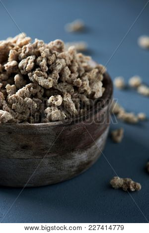 closeup of some chunks of textured soy protein in a rustic wooden bowl, on a gray wooden table