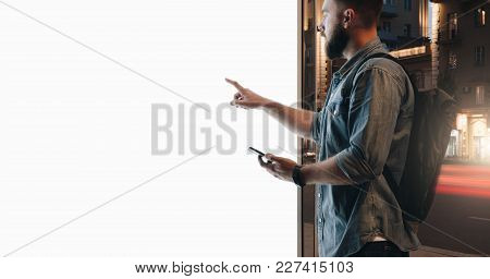 Summer Night. Young Hipster Bearded Man Stands On City Street And Touches Large Glowing Touchscreen