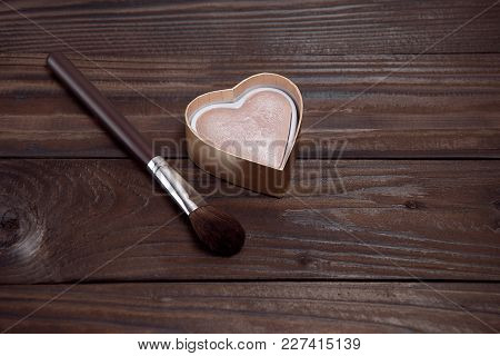Professional Makeup Brush With Highlighter On Brown Wooden Background