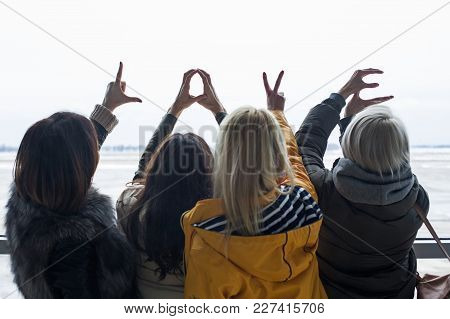 Backs Of Four Females Gazing At Runway And Showing Love Word With Fingers