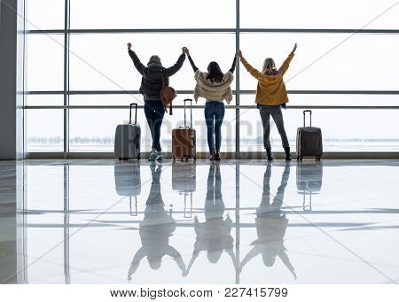 Three Females Standing With Their Backs Near Airport Window And Holding Hands. Baggage Is Nearby
