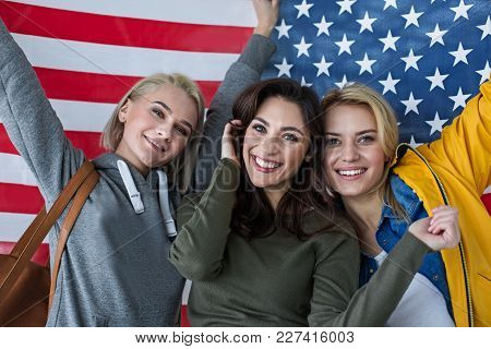 Nationalism Concept. Portrait Of Excited Women Standing Close. Banner Of United States Is On Backgro