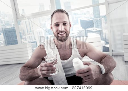 Vitamin Requirements. Appealing Bearded Young Sportsman Holding Glass With Water While Consuming Vit