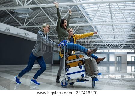 Delighted Women Entertaining At The Airport. They Are Carrying Luggage Trolley With Girl Sitting On