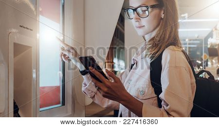 Summer Night. Young Woman In Eyeglasses With Backpack Stands On City Street, Touches Digital Display