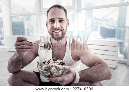Fast And Healthy. Pleased Satisfied Pretty Sportsman Using Fork While Eating Salad And Gazing At Cam