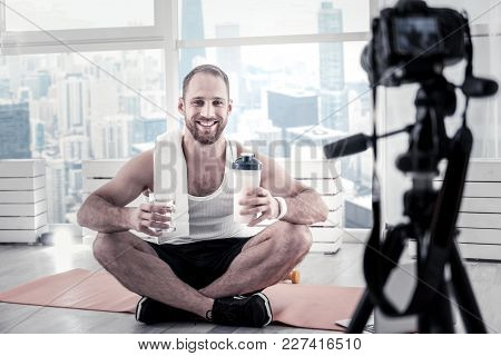 Water Balance. Energetic Happy Active Sportsman Carrying Bottle While Grinning And Filming Video