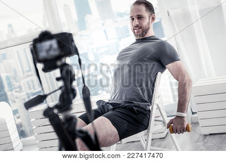 Fitness Goal. Attractive Nice Male Blogger Sitting On Chair While Using Camera And Filming Video