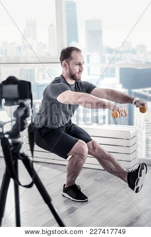 Sport For Everyone. Bearded Attractive Male Blogger Holding Dumbbells While Rising Leg And Performin