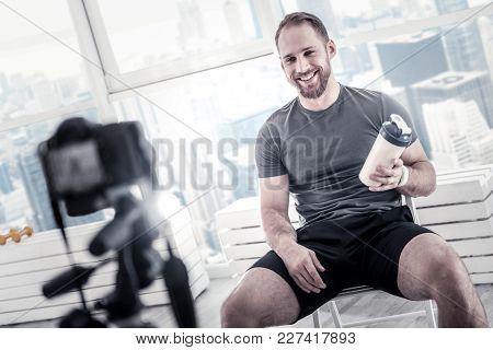 After Exercise Session. Cheerful Gay Male Blogger Carrying Bottle While Grinning And Sitting On Chai