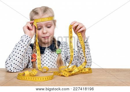 Little Girl Measuring Tape Measure With Her Head Sitting At A Wooden Table Isolated On A White Backg