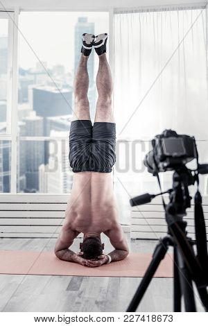 Diligent Workout. Impressing Wonderful Male Blogger Demonstrating Headstand While Using Camera And P