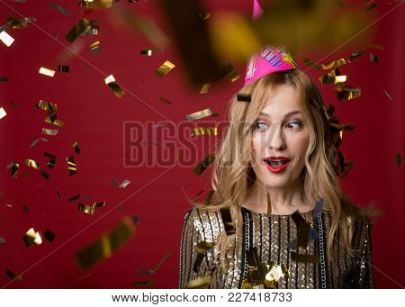 Portrait Of Surprised Female In Cone Cap Standing Surrounded By Sparkling Confetti And Looking Aside