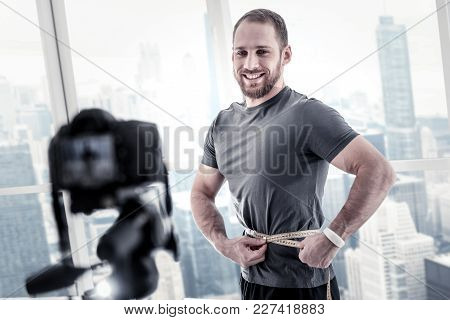 Minus Centimeter. Cheerful Glad Male Blogger Applying Meter While Recording Video And Smiling