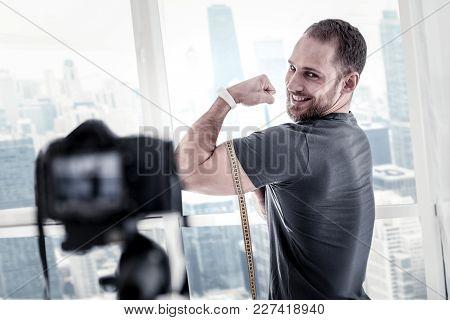 Bigger Biceps. Vigorous Joyful Male Blogger Measuring Biceps Size While Grinning And Updating Blog