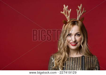 Portrait Of Well Dressed Lady Wearing Funny Reindeer Headband, She Is Looking At Camera And Smiling.