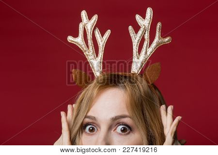Close Up Of Female Head Wearing Golden Reindeer Antlers Headband, Looking Amazed. Isolated On Red Ba