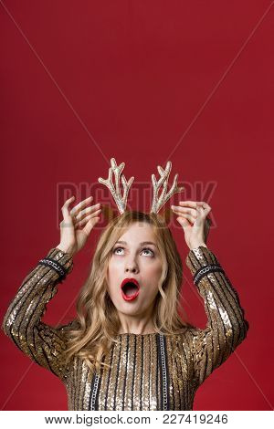 Portrait Of Female Person Putting On Horns Of Deer On Head With Wonder. Isolated On Red Background.