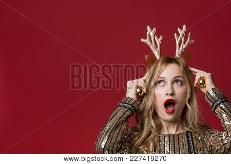 Portrait Of Astonished Woman Wearing Horns And Bells Of A Deer. Copy Space In Left Side. Isolated On