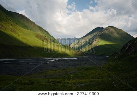 Mountain Valley With River And Mountain Range At The Background.
