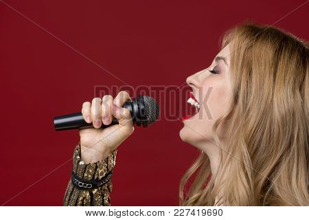 Side View Profile Of Peaceful Lady Holding Mike And Singing With Eyes Closed. Isolated On Red Backgr