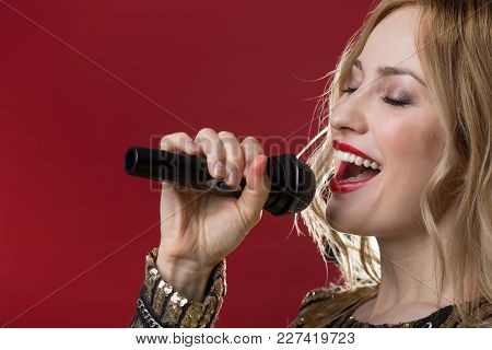 Tranquil Attractive Woman Demonstrating Singing Talent With Mike In Hand. Isolated On Red Background